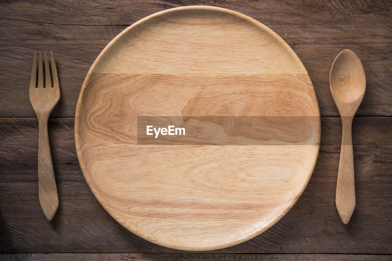 Directly Above Shot Of Wooden Plate With Cutlery On Table