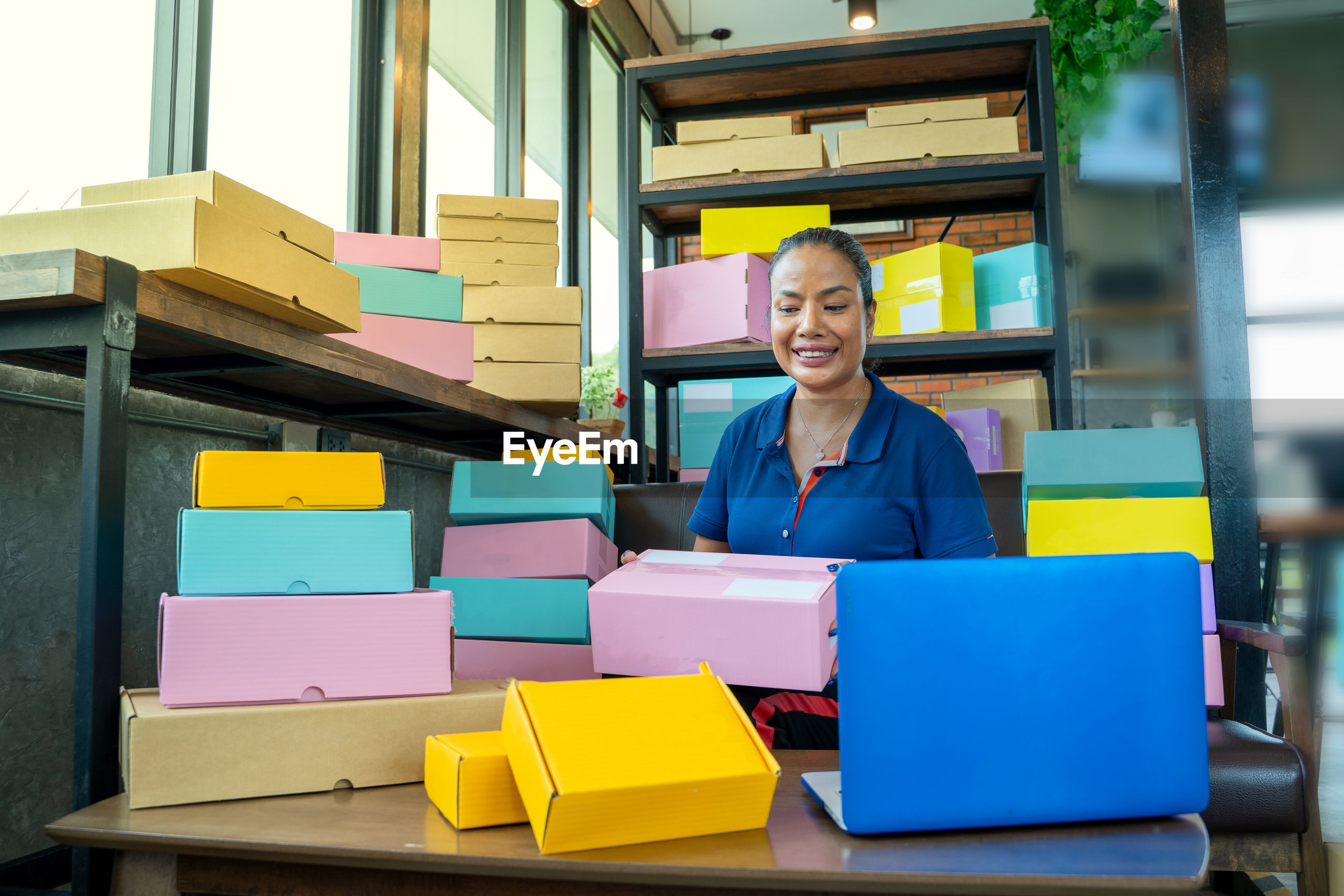 PORTRAIT OF A SMILING YOUNG MAN SITTING ON STACK OF COLORFUL