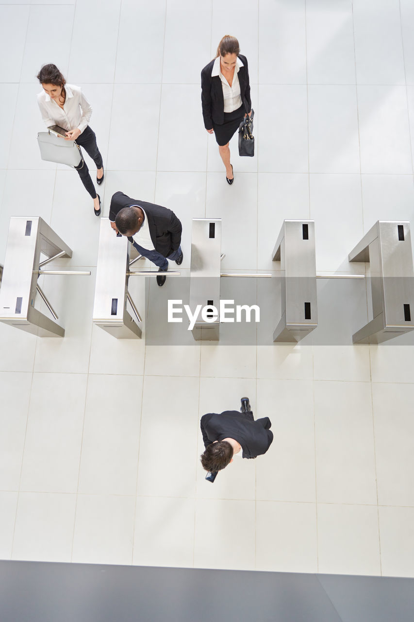 HIGH ANGLE VIEW OF PEOPLE STANDING ON FLOORING