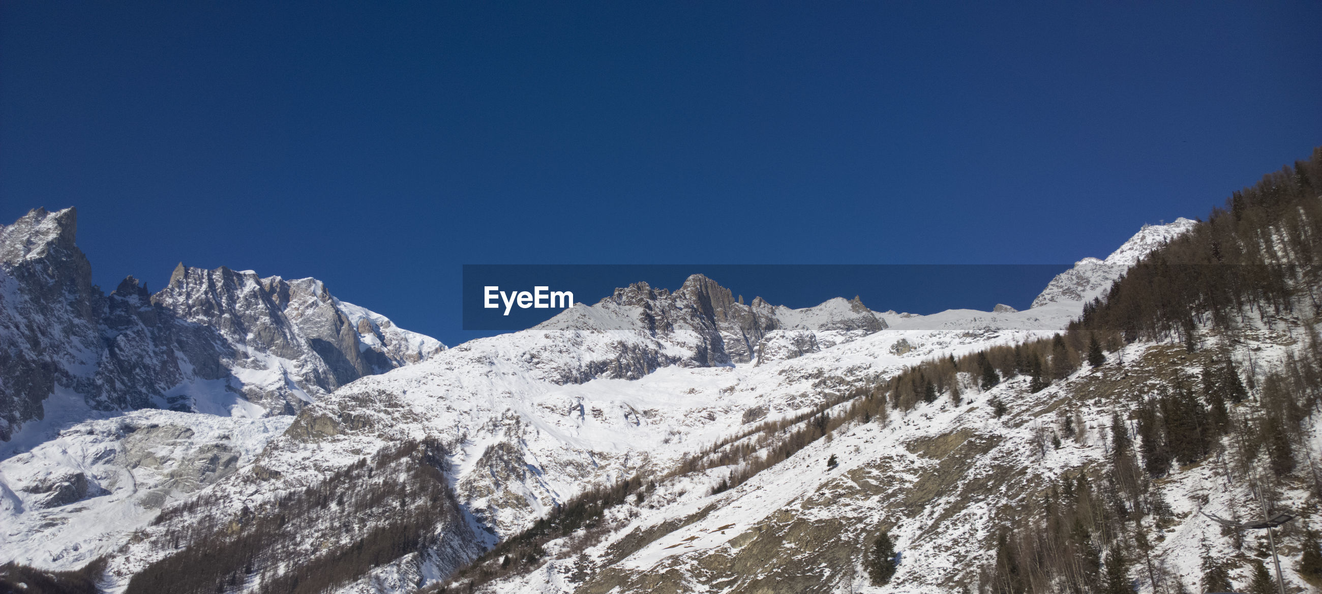 LOW ANGLE VIEW OF SNOWCAPPED MOUNTAINS AGAINST CLEAR SKY
