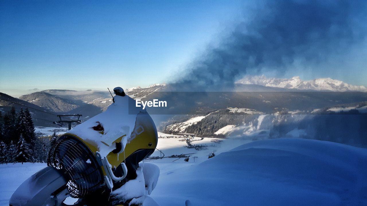 Machine Spraying Snow Against Mountains