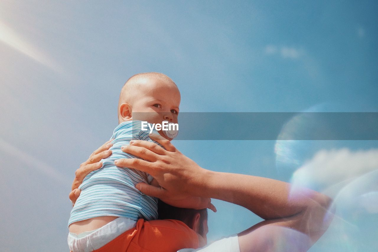 Father Carrying Baby Boy Against Sky