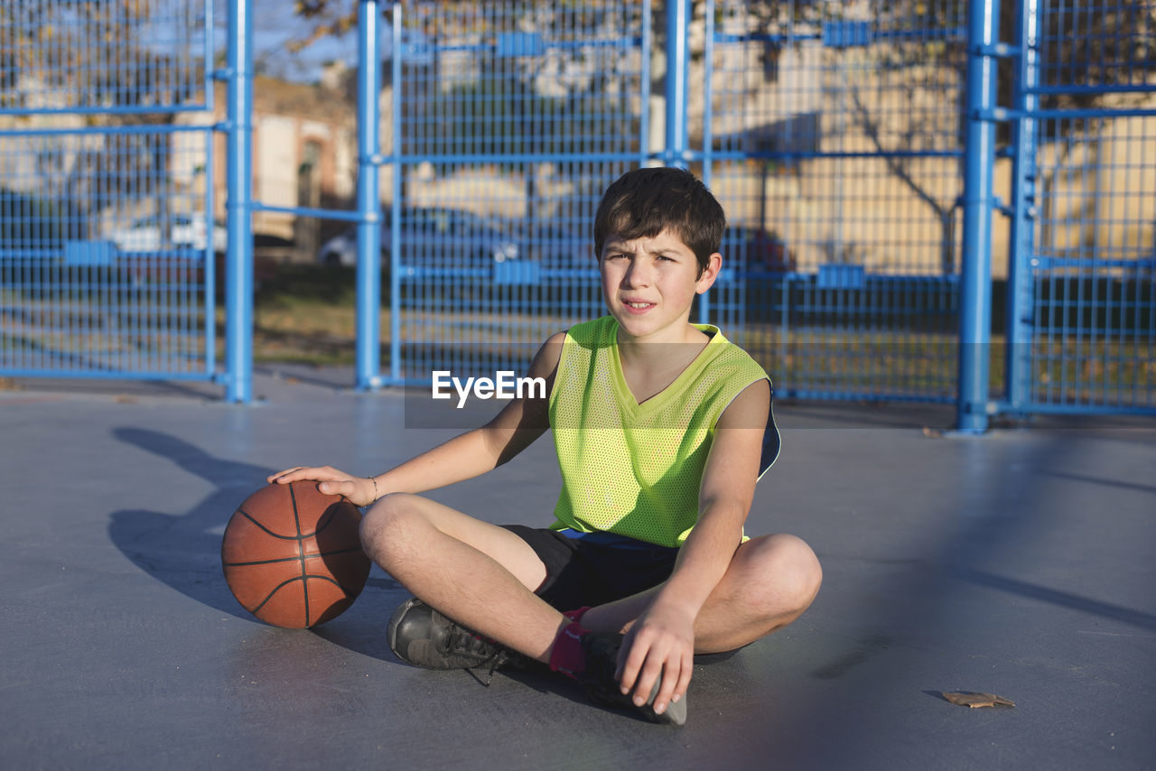 Portrait Of Boy Holding Basketball While Sitting In Court