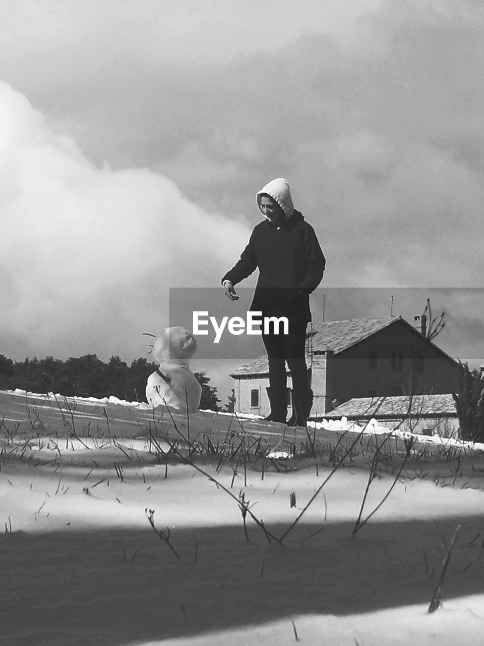 Woman Standing By Snowman On Field Against Cloudy Sky
