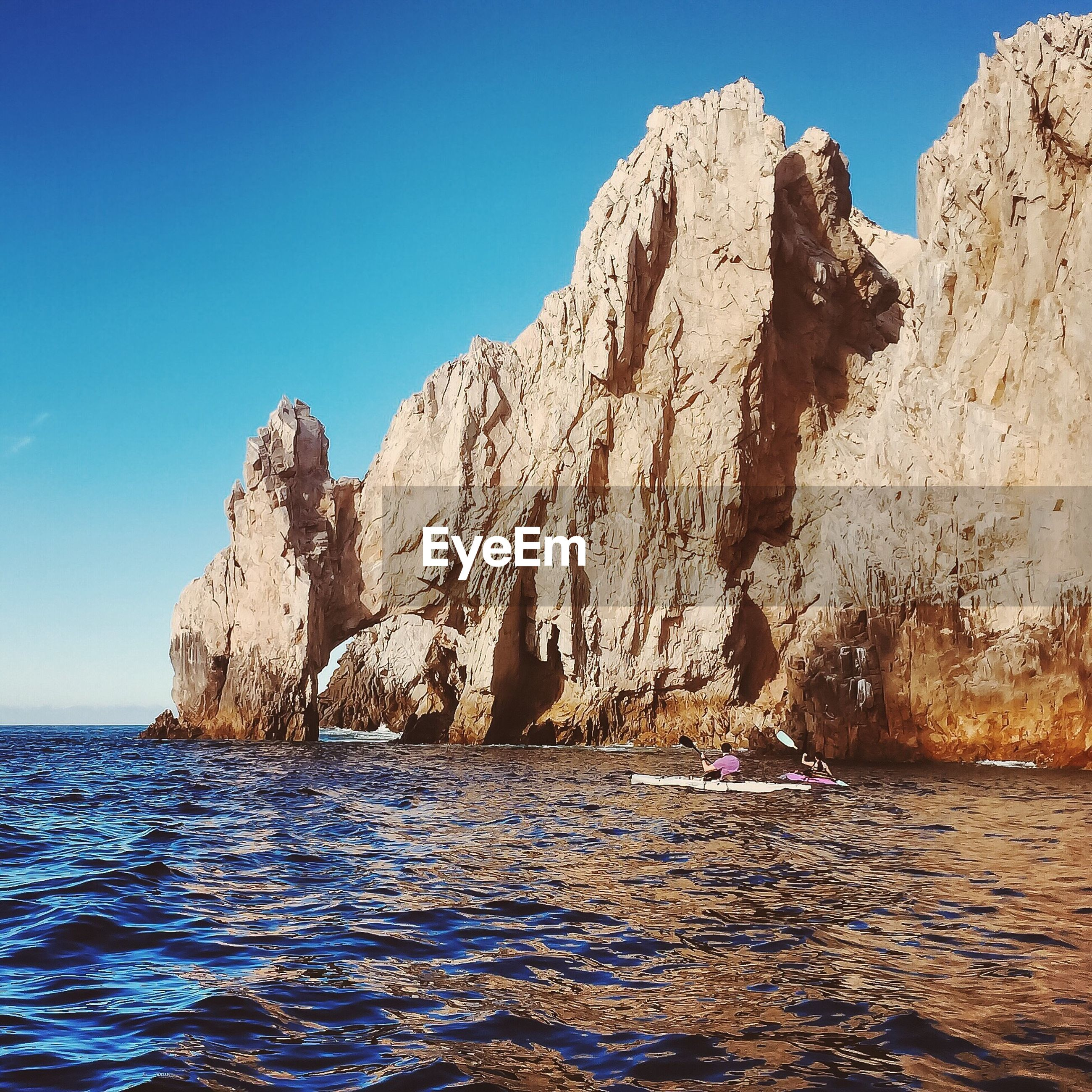 SCENIC VIEW OF ROCK FORMATION IN SEA AGAINST CLEAR BLUE SKY