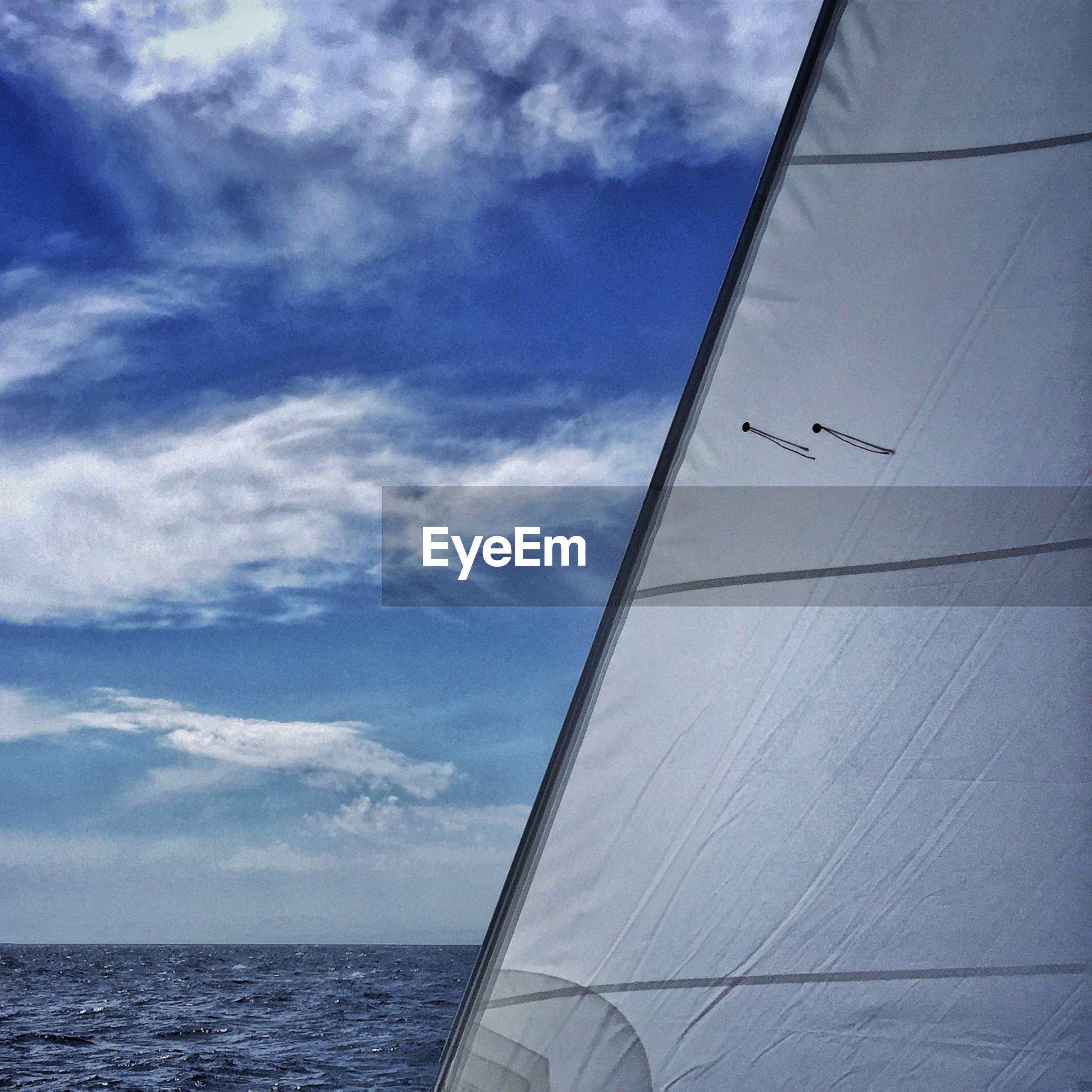 Tarpaulin sheet of sailboat on sea against wispy blue sky