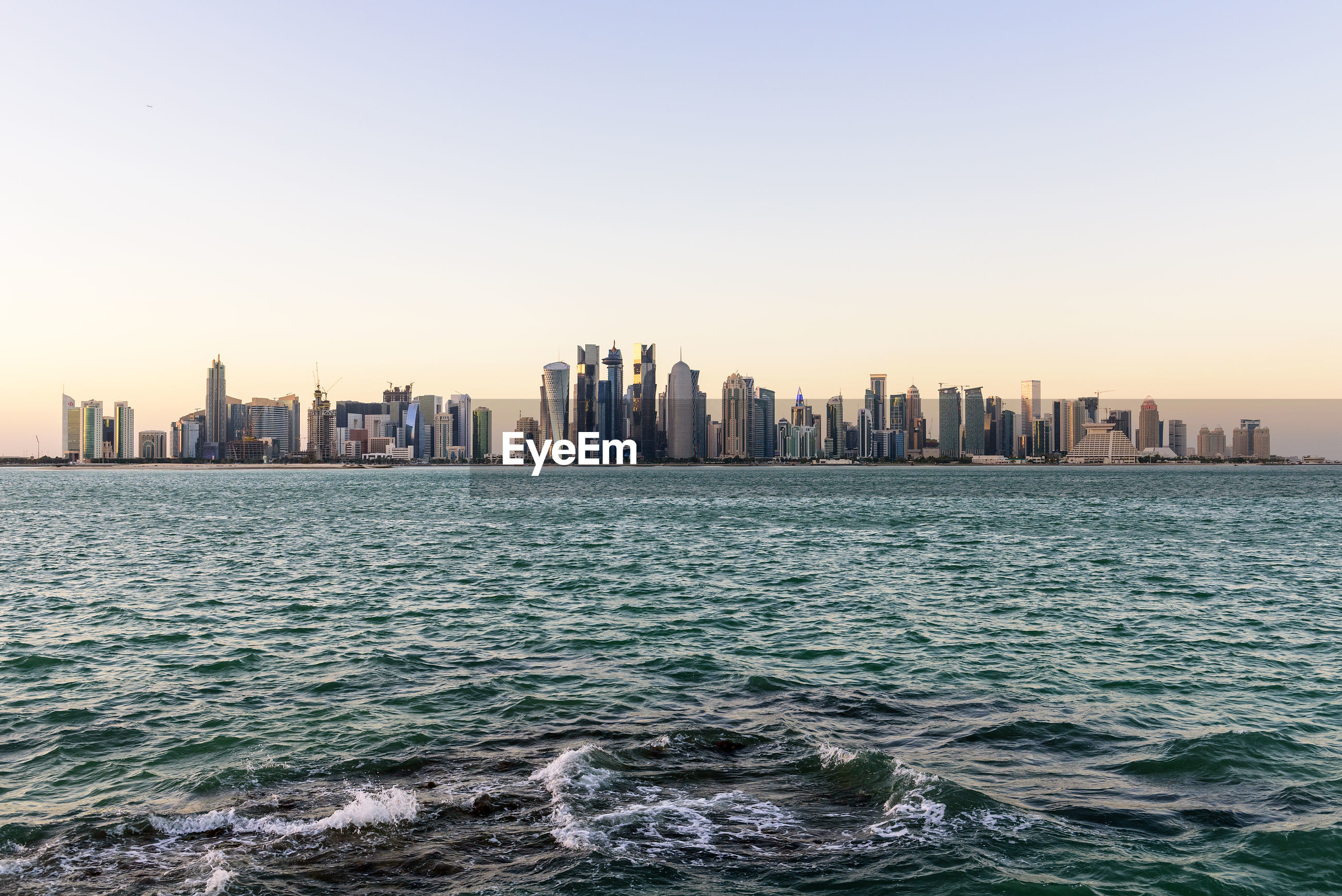 Sea and cityscape against clear sky