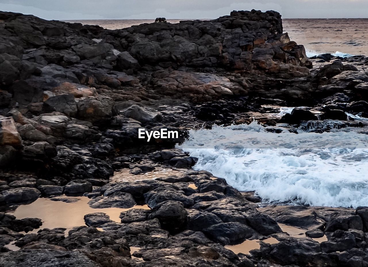 rock - object, rock formation, nature, sea, no people, geology, beauty in nature, rock, water, motion, outdoors, wave, day, power in nature, scenics, beach, lava, sky, clear sky