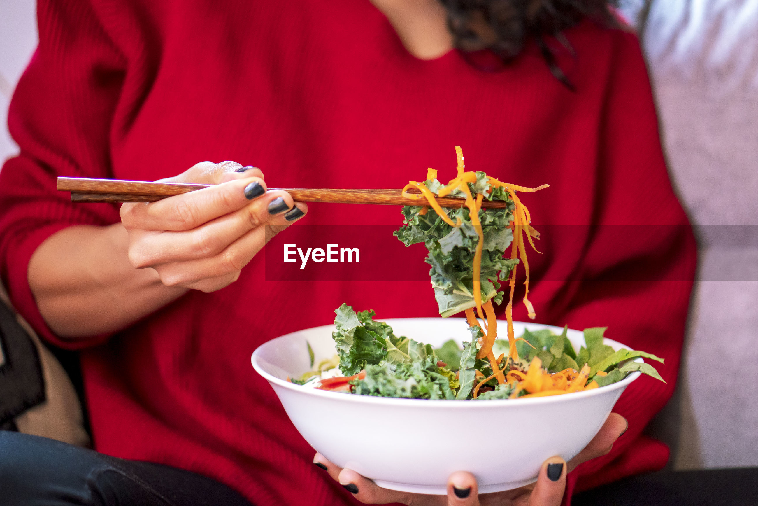 MIDSECTION OF WOMAN HOLDING BOWL WITH RED CHILI PEPPERS