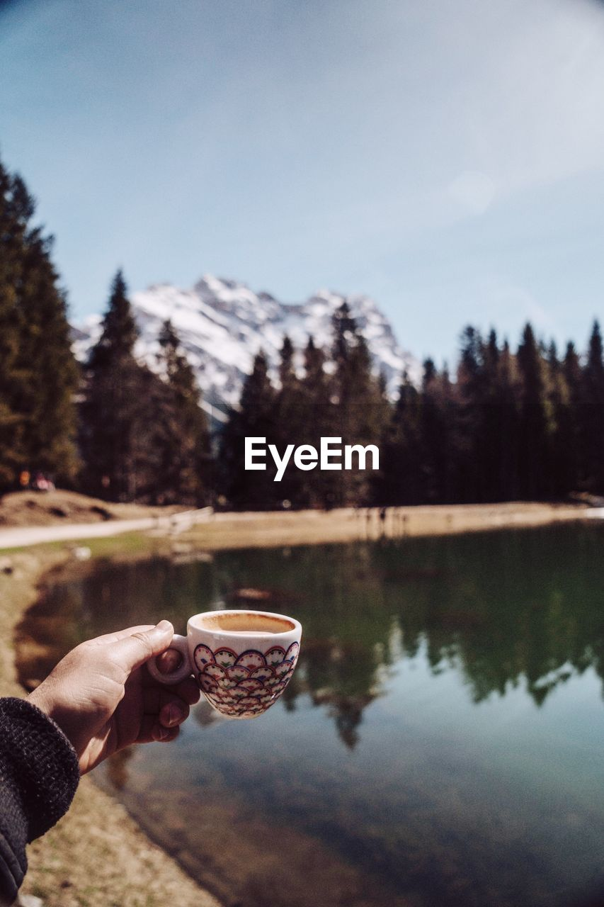 Cropped Hand Holding Coffee Cup By Lake