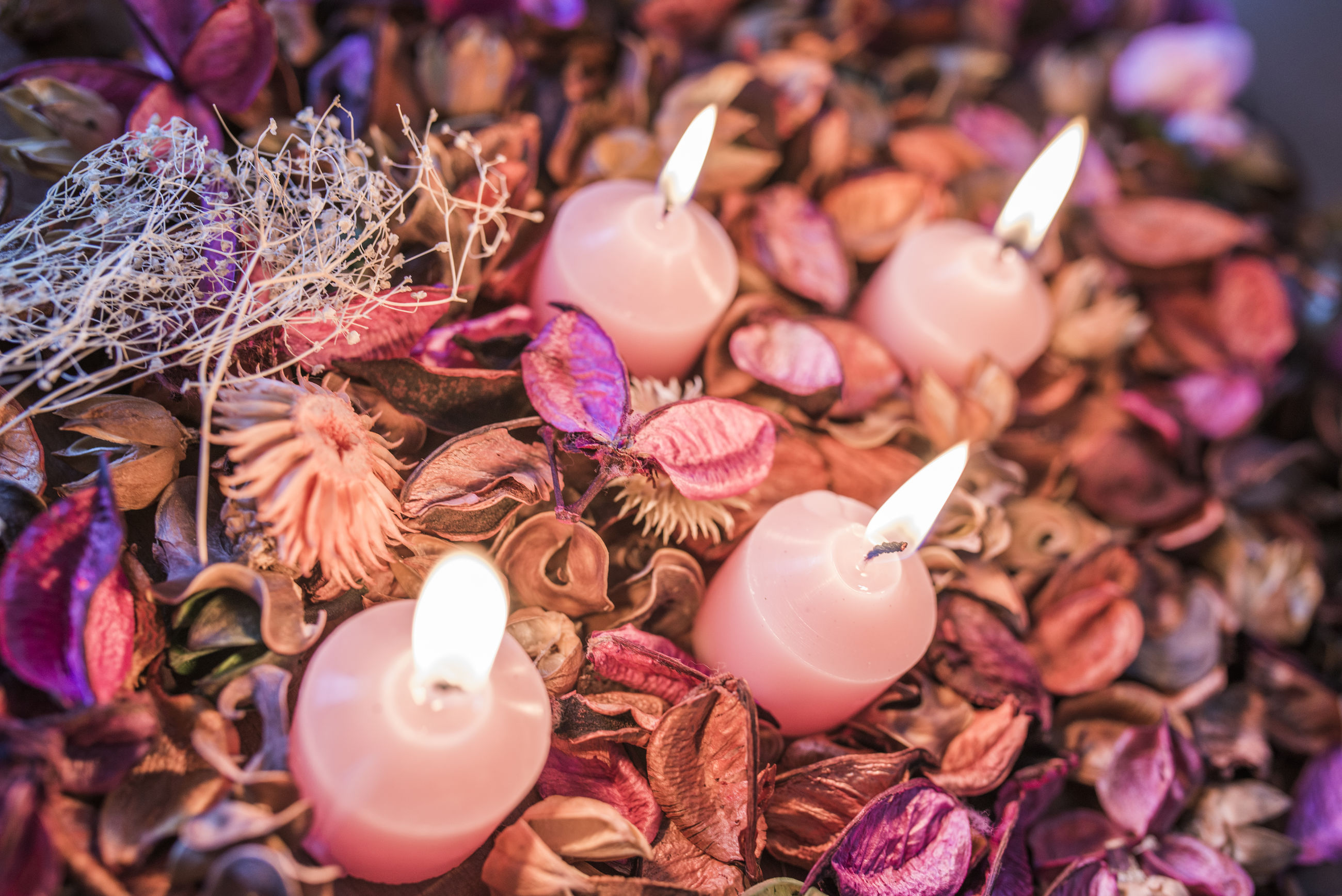 High angle view of illuminated candles on flower petals