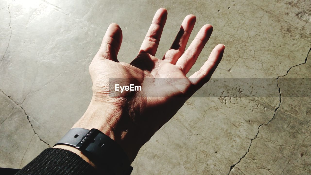 Close-Up Of Hand Wearing Wristwatch Against Wall