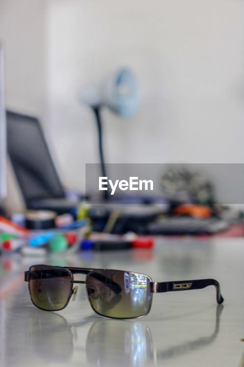 table, technology, indoors, glasses, still life, computer, connection, no people, close-up, wireless technology, desk, selective focus, office, sunglasses, eyeglasses, personal accessory, focus on foreground, reflection, communication, computer equipment, eyewear