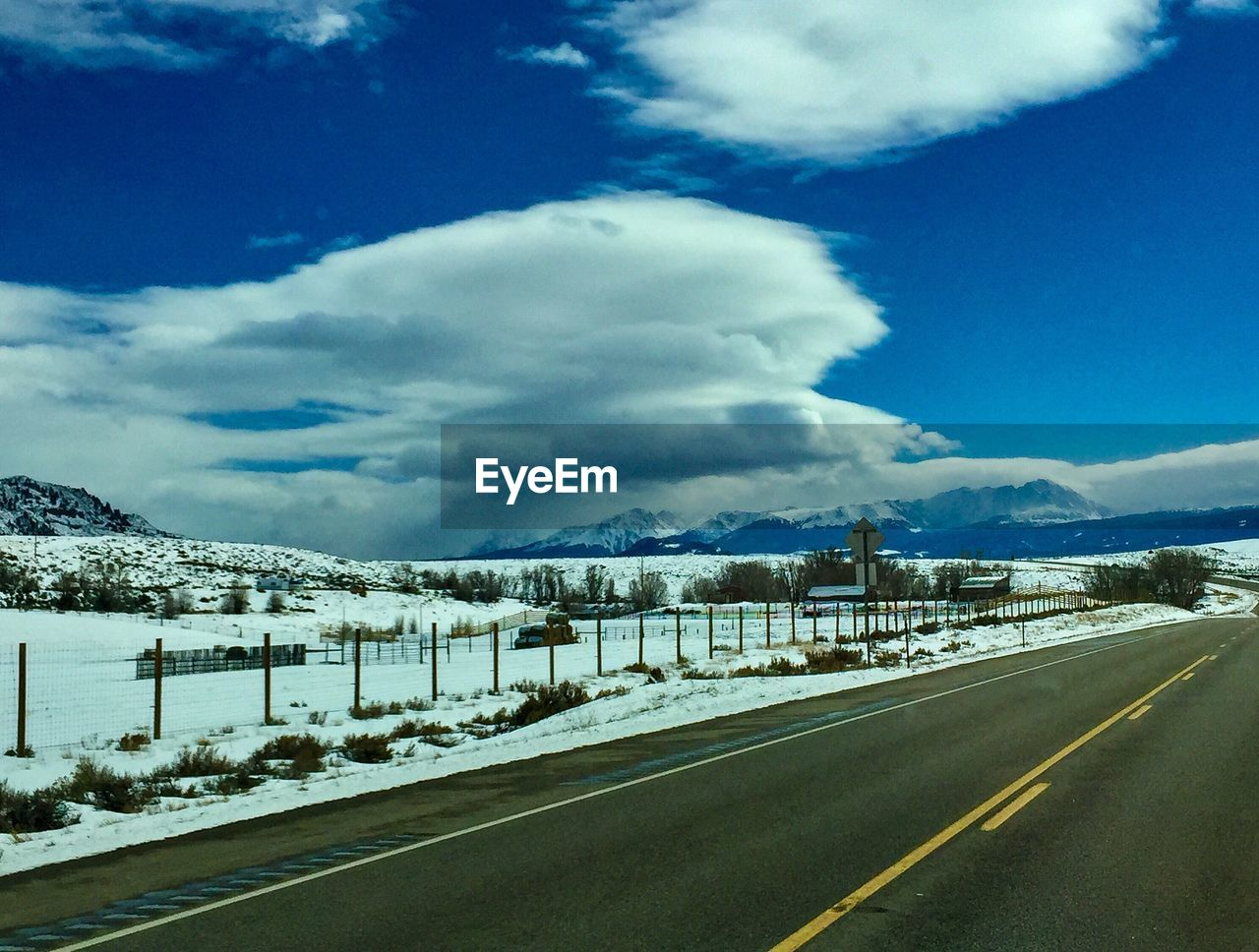 cloud - sky, sky, transportation, road, winter, snow, cold temperature, nature, no people, direction, day, mountain, beauty in nature, the way forward, sign, road marking, scenics - nature, marking, diminishing perspective, outdoors, snowcapped mountain, dividing line, crash barrier