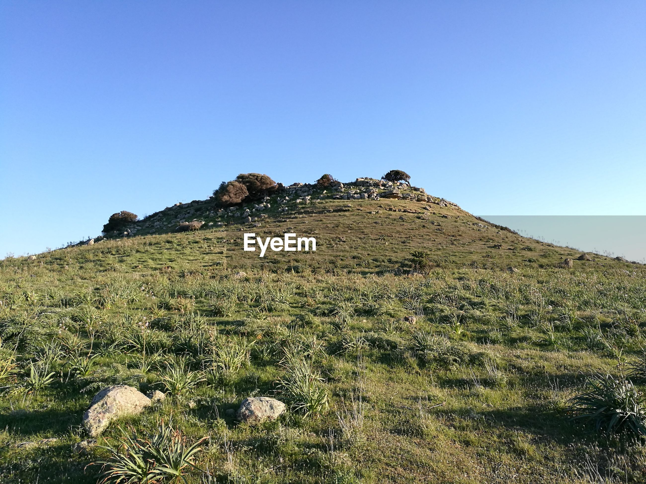 LOW ANGLE VIEW OF ROCKS ON MOUNTAIN AGAINST CLEAR BLUE SKY