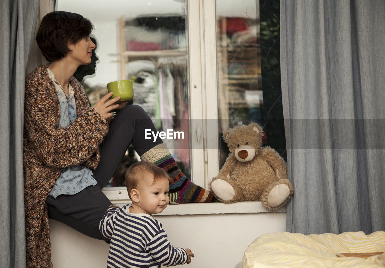 Woman having drink while siting on window
