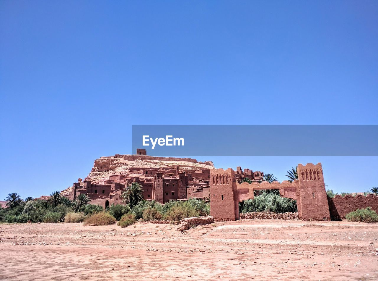 sky, blue, architecture, built structure, clear sky, copy space, history, the past, nature, day, ancient, land, building exterior, plant, travel destinations, no people, sunlight, tree, building, landscape, outdoors, ancient civilization, arid climate, climate, ruined