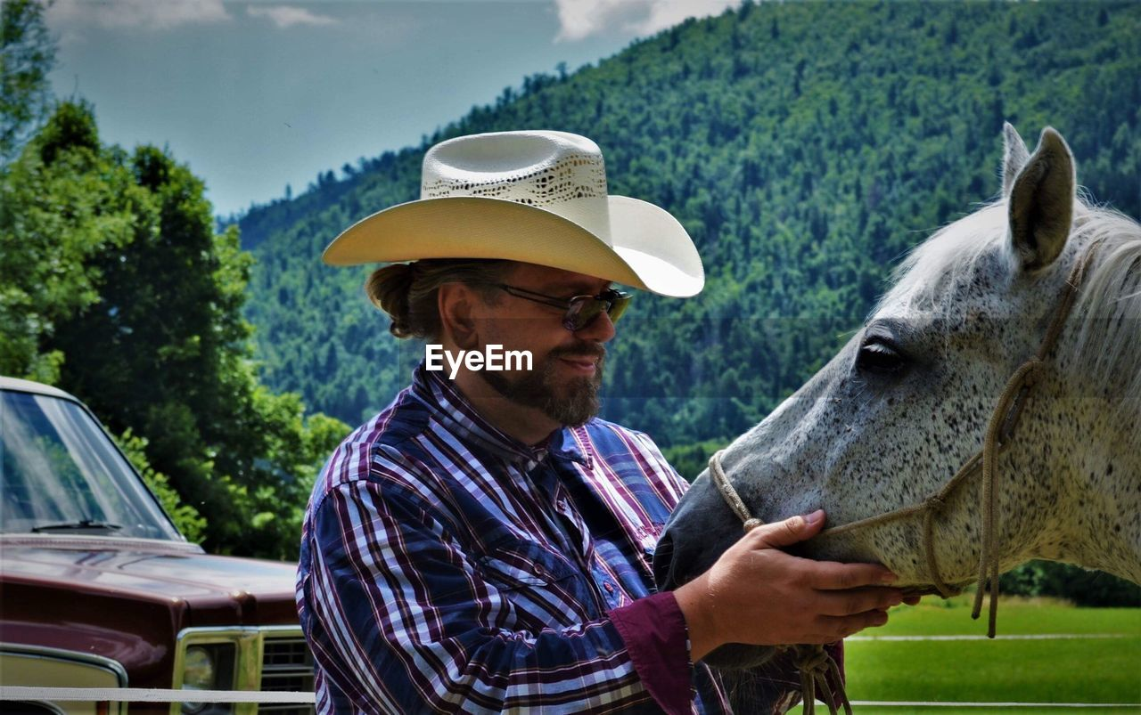 Smiling Man Looking At Horse While Standing Against Mountain