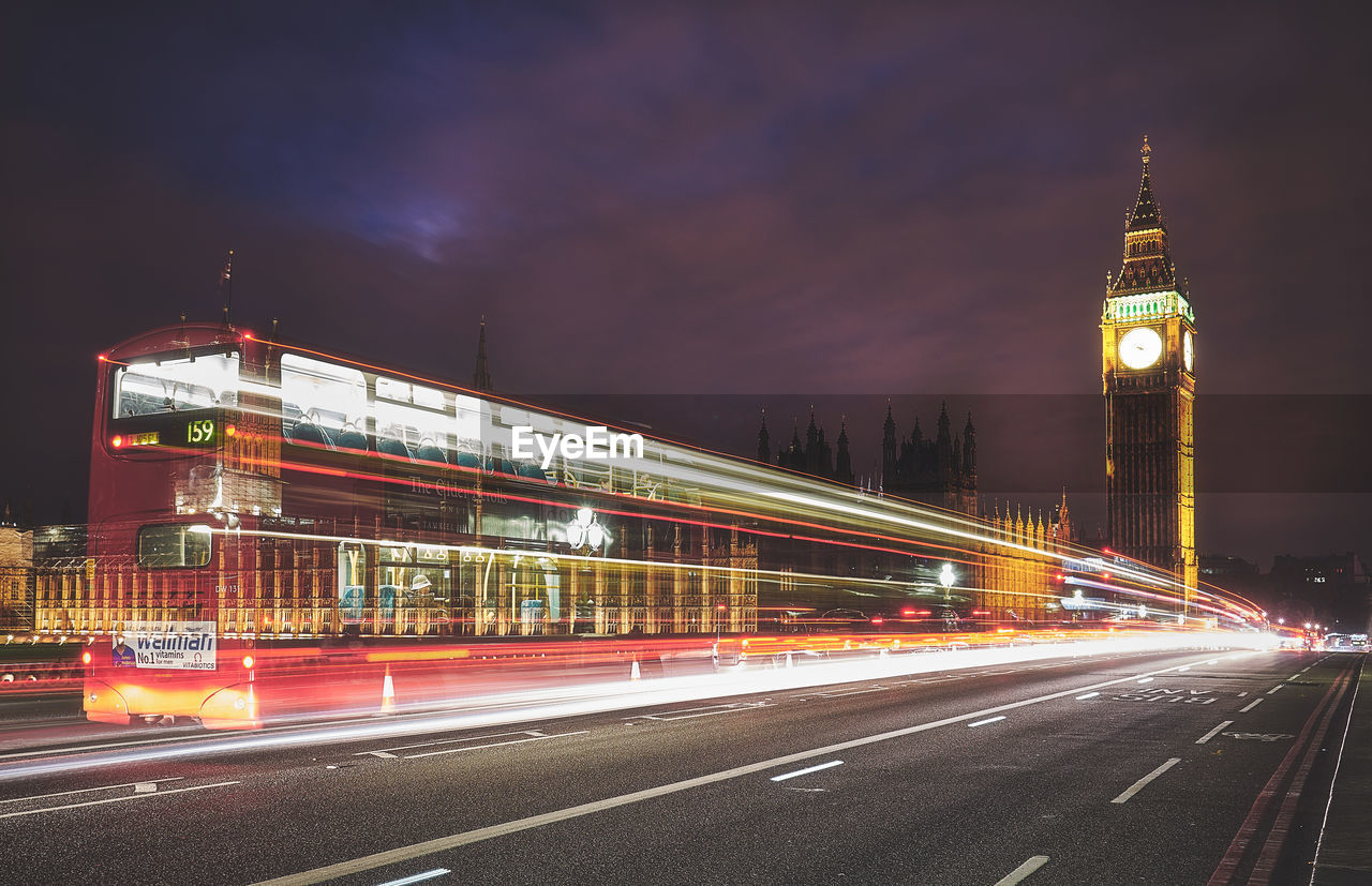 architecture, built structure, illuminated, long exposure, building exterior, city, motion, night, light trail, speed, blurred motion, travel destinations, road, sky, street, tower, transportation, city life, building, no people, tall - high, outdoors, office building exterior, double-decker bus, skyscraper