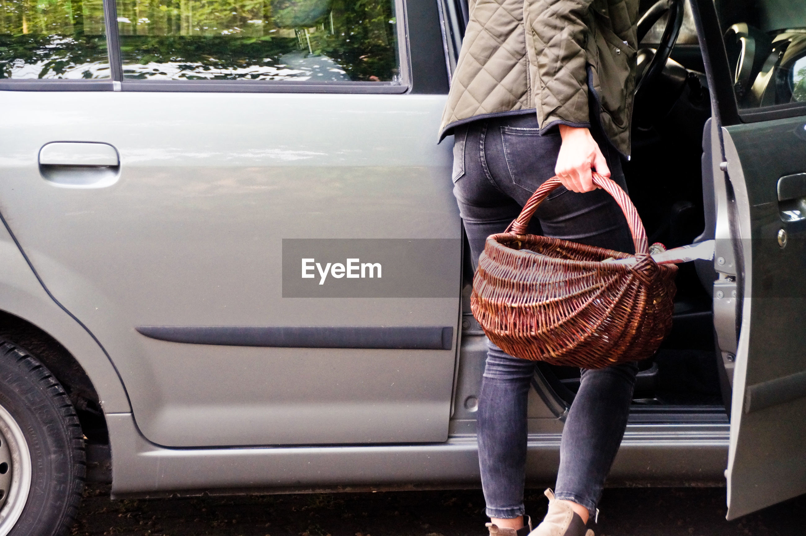 Low section of woman holding basket while entering in car
