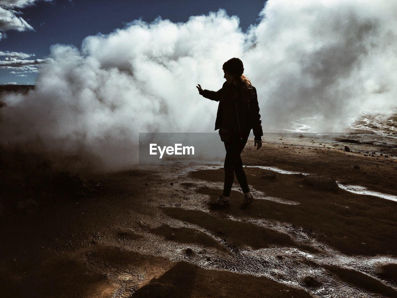 Full Length Of Woman Walking By Geyser Emitting Smoke