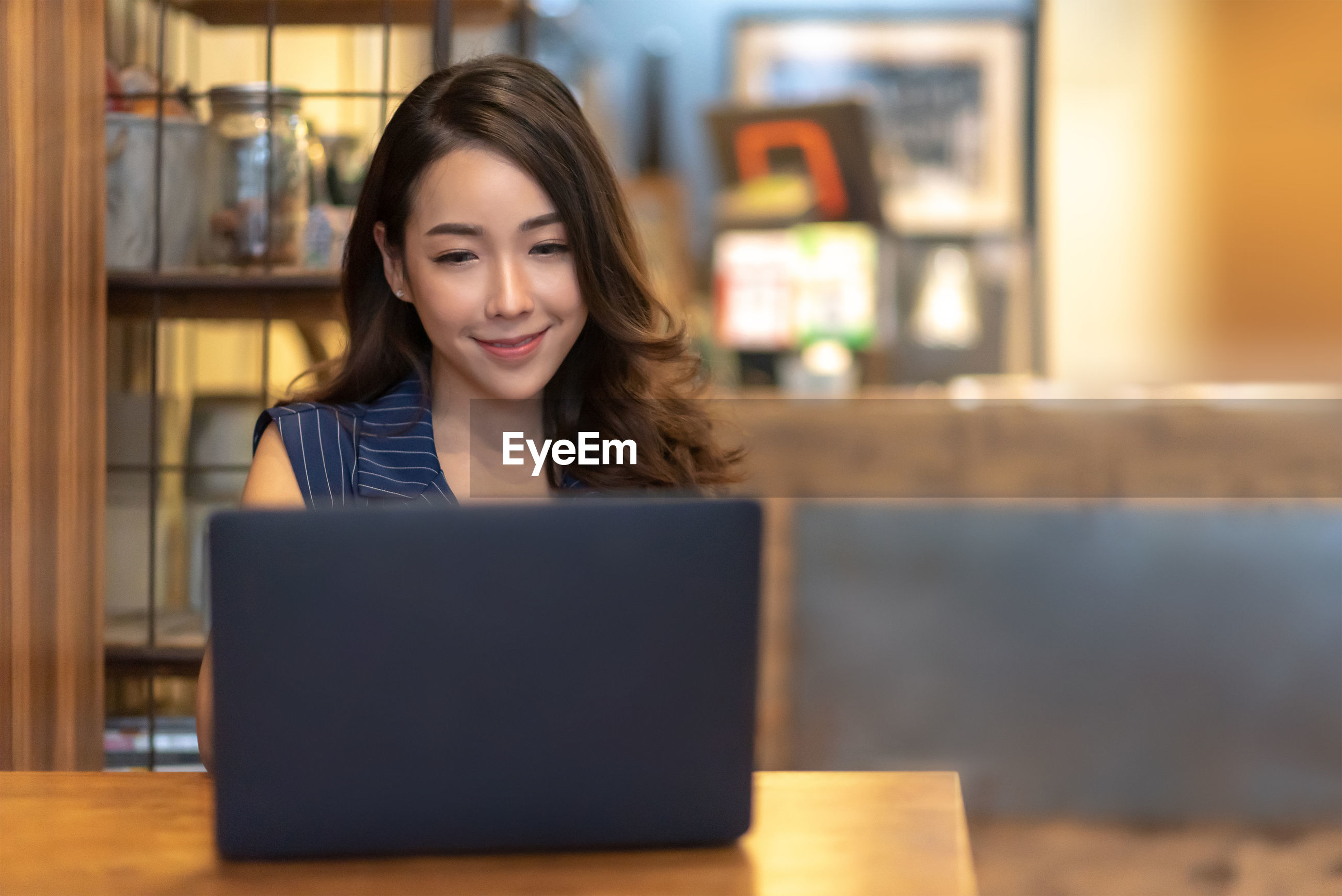 Businesswoman using laptop on table in cafe