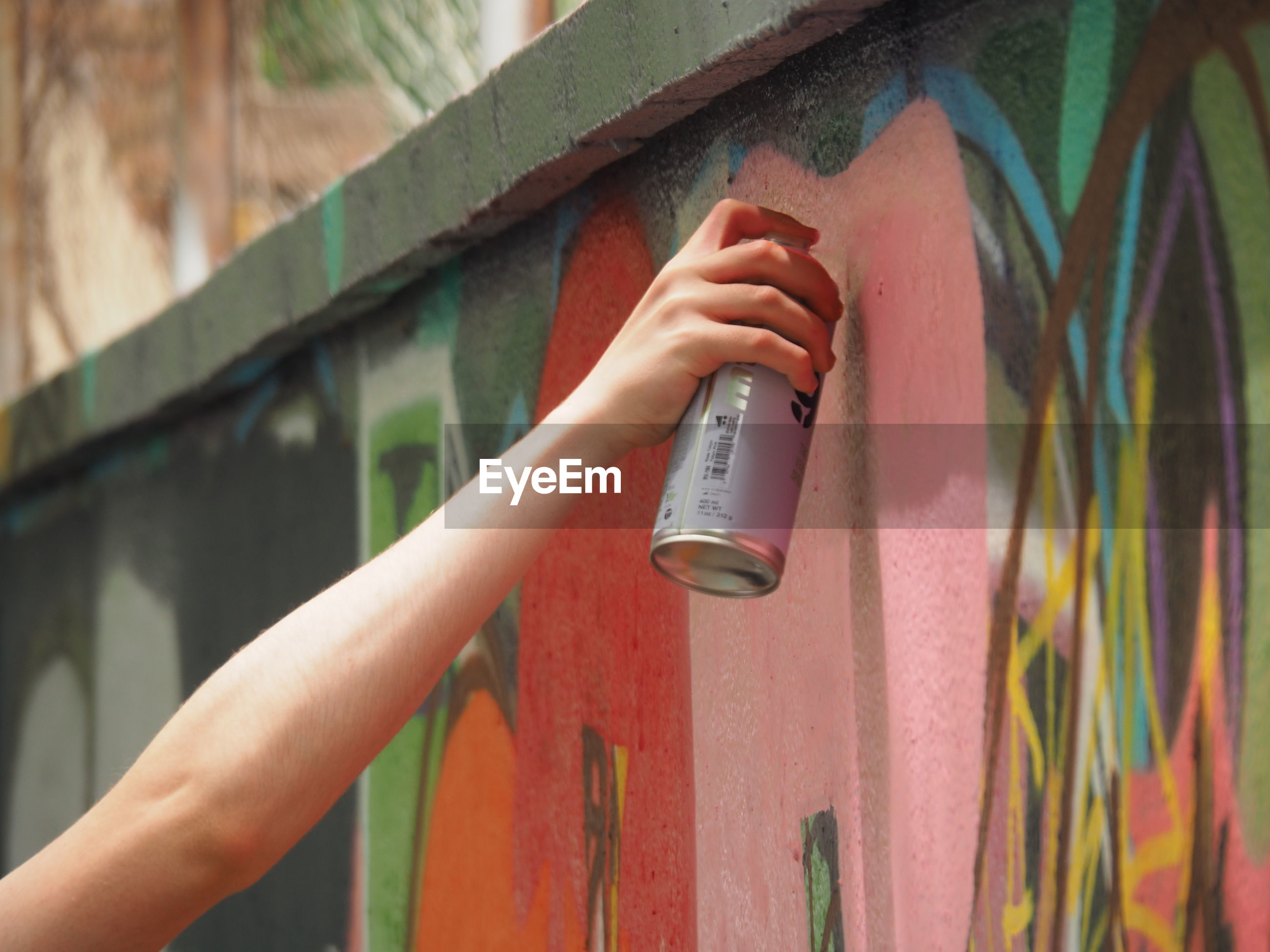 Cropped image of person painting graffiti on wall