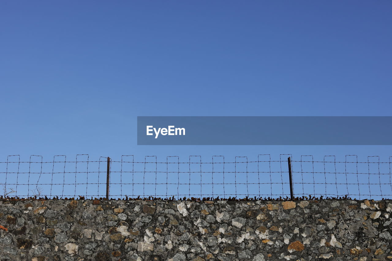 copy space, sky, barrier, clear sky, fence, boundary, day, blue, safety, nature, metal, security, protection, no people, wire, solid, wall - building feature, wall, outdoors, surrounding wall, stone wall