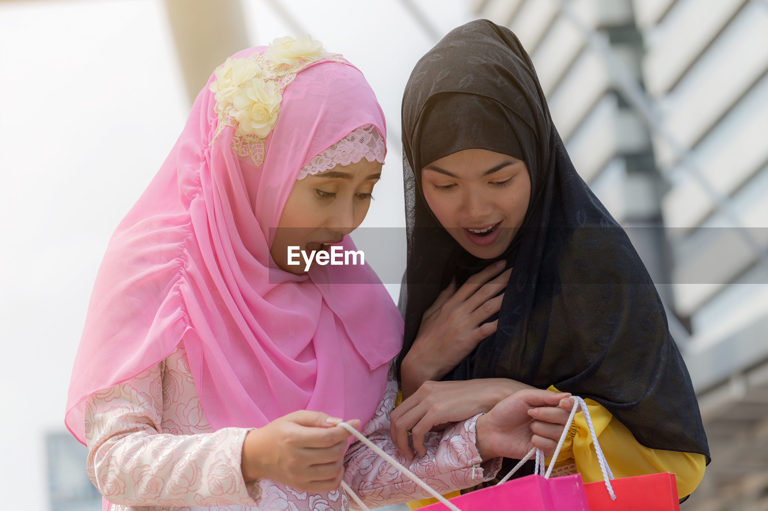 Shocked female friends looking at shopping bags in city
