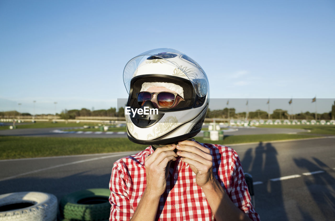 one person, helmet, transportation, portrait, headwear, sky, front view, crash helmet, mode of transportation, leisure activity, real people, road, day, headshot, sports helmet, unrecognizable person, lifestyles, nature, sport, obscured face, outdoors