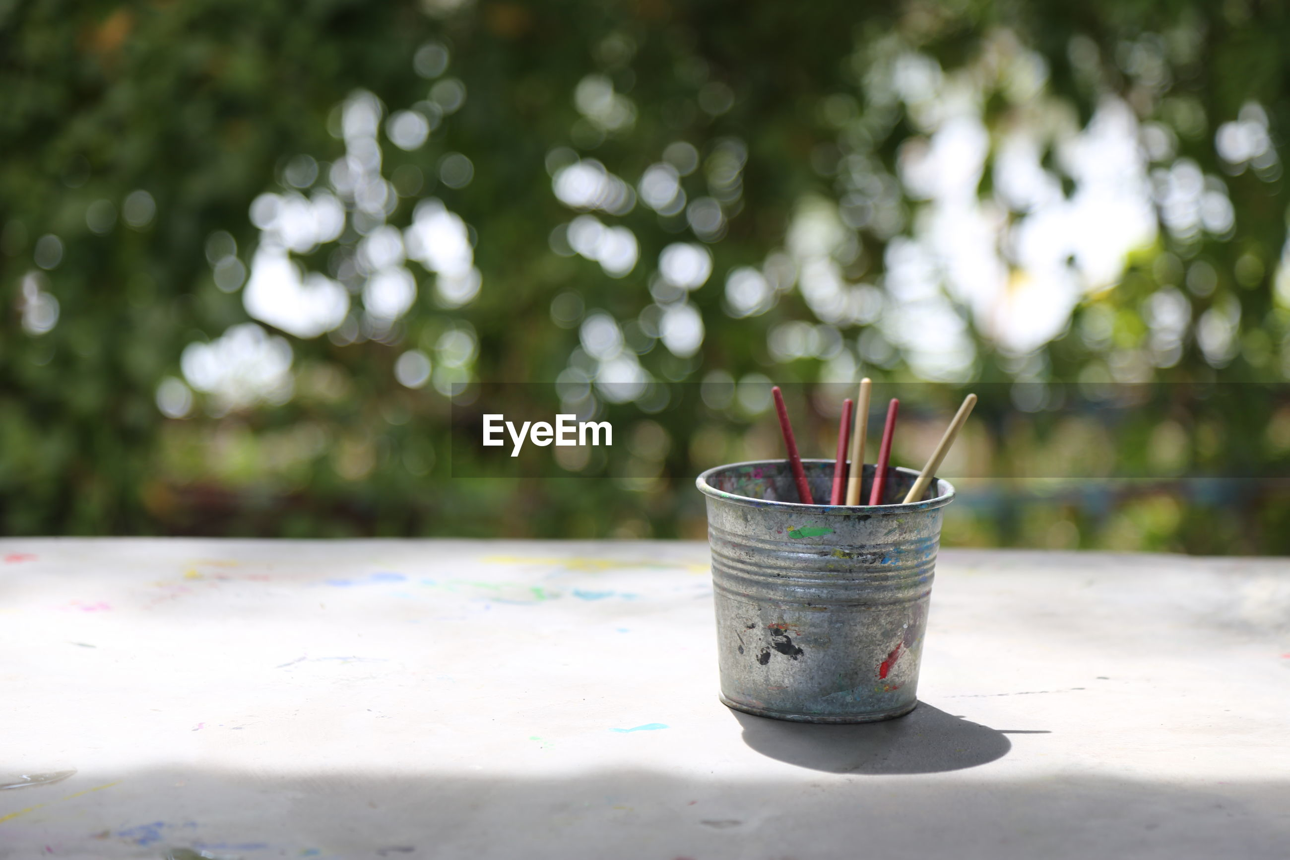Paintbrushes in container against trees
