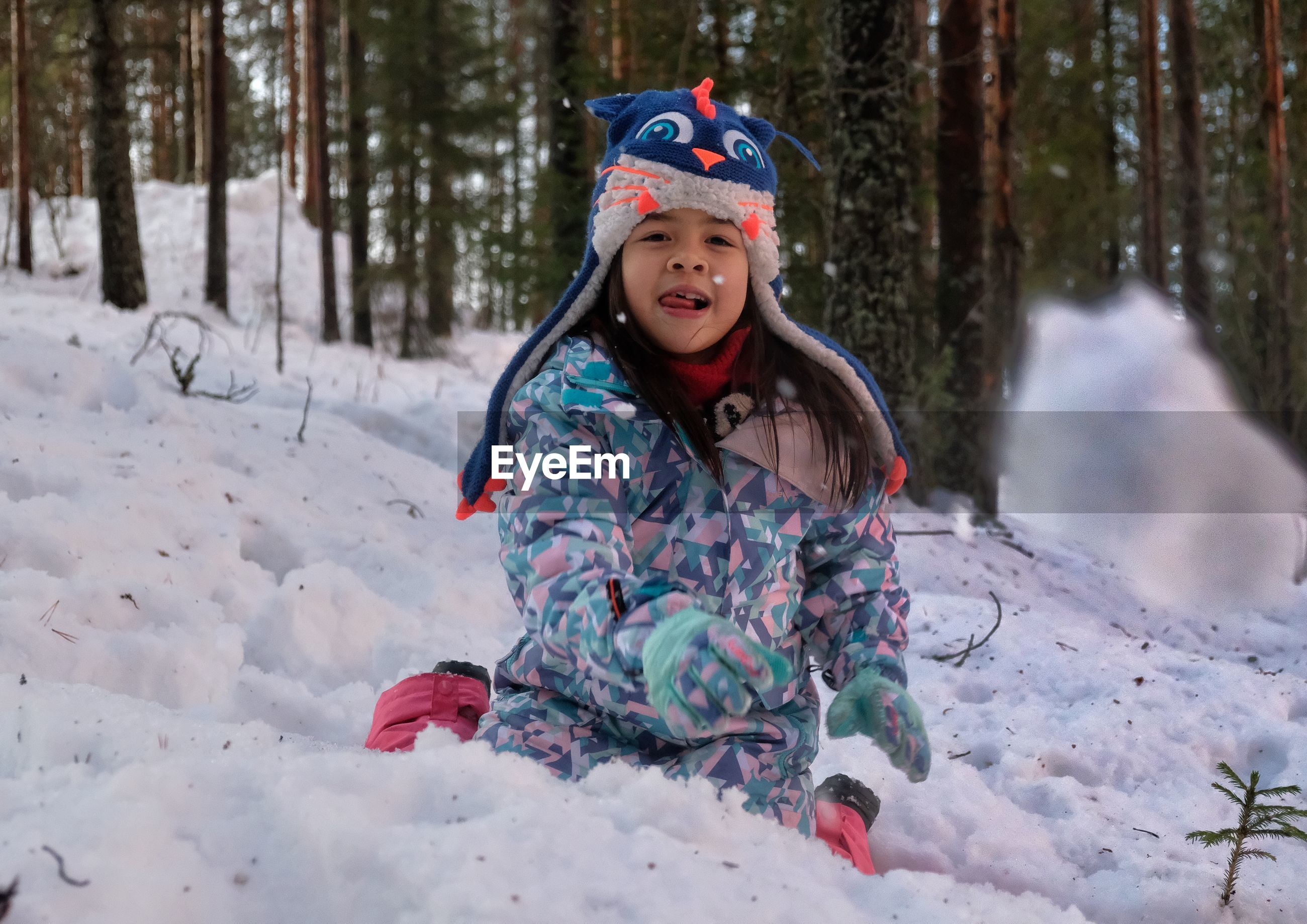 Portrait of cute girl in warm clothes on snow