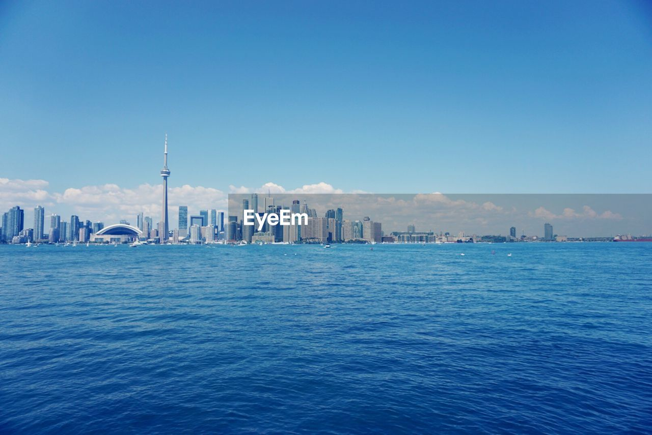 Distant View Of Cn Tower And City By Sea Against Blue Sky