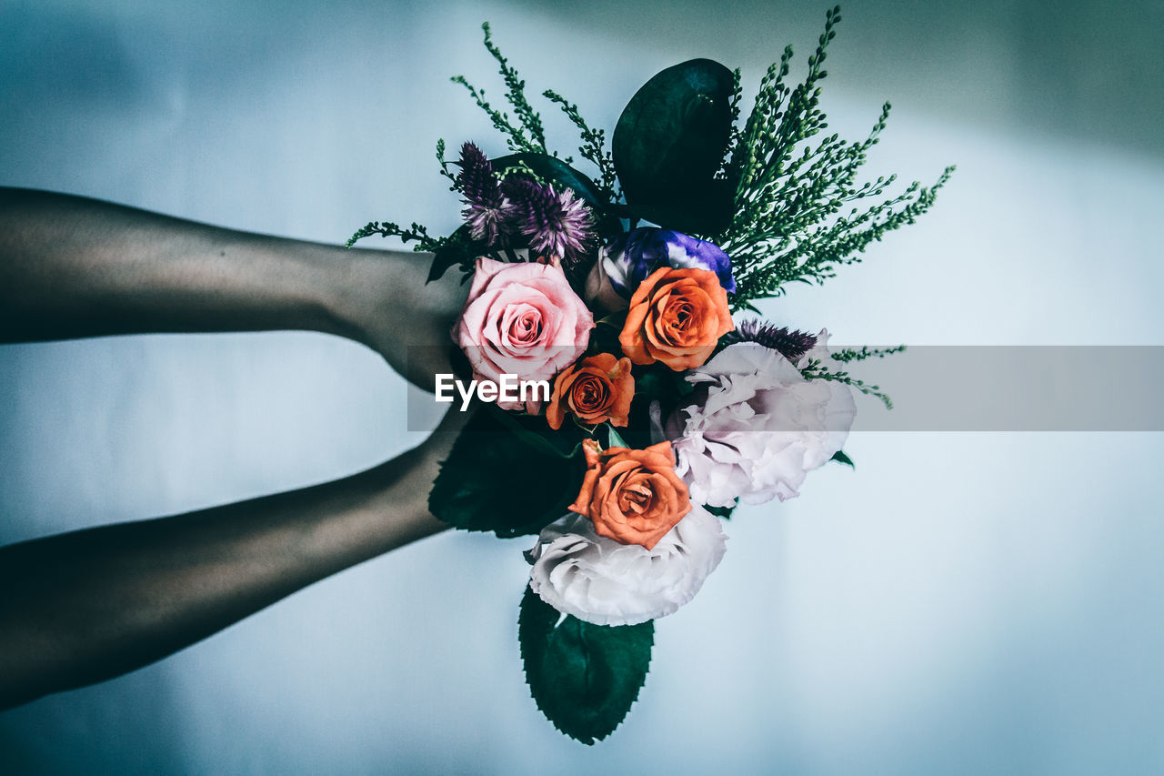 Cropped hands holding rose bouquet