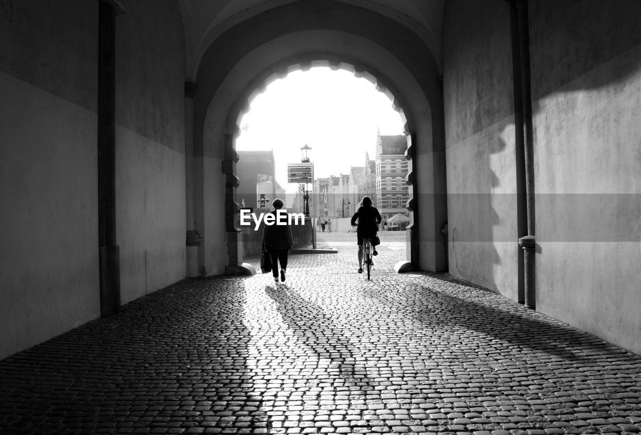 walking, real people, arch, architecture, built structure, two people, the way forward, full length, lifestyles, rear view, men, women, day, togetherness, indoors, building exterior, adult, people