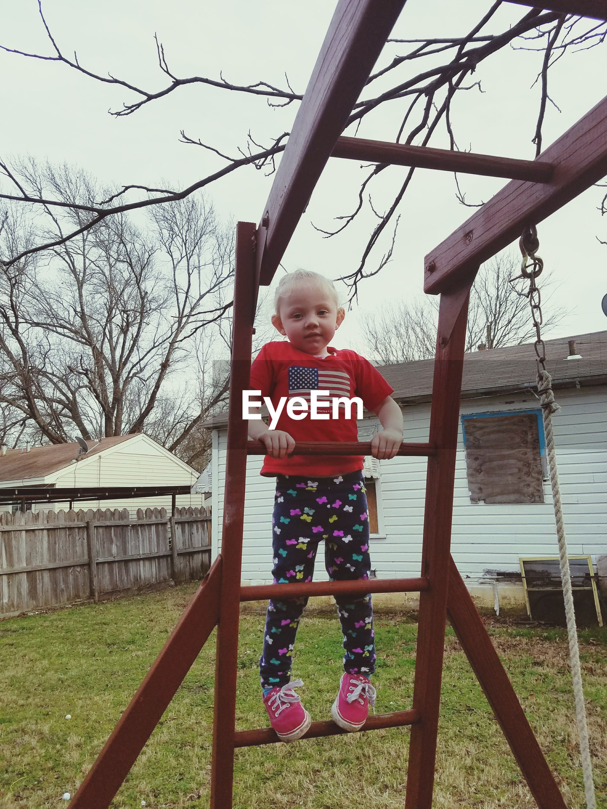 Full length portrait of cute girl standing on monkey bars in yard