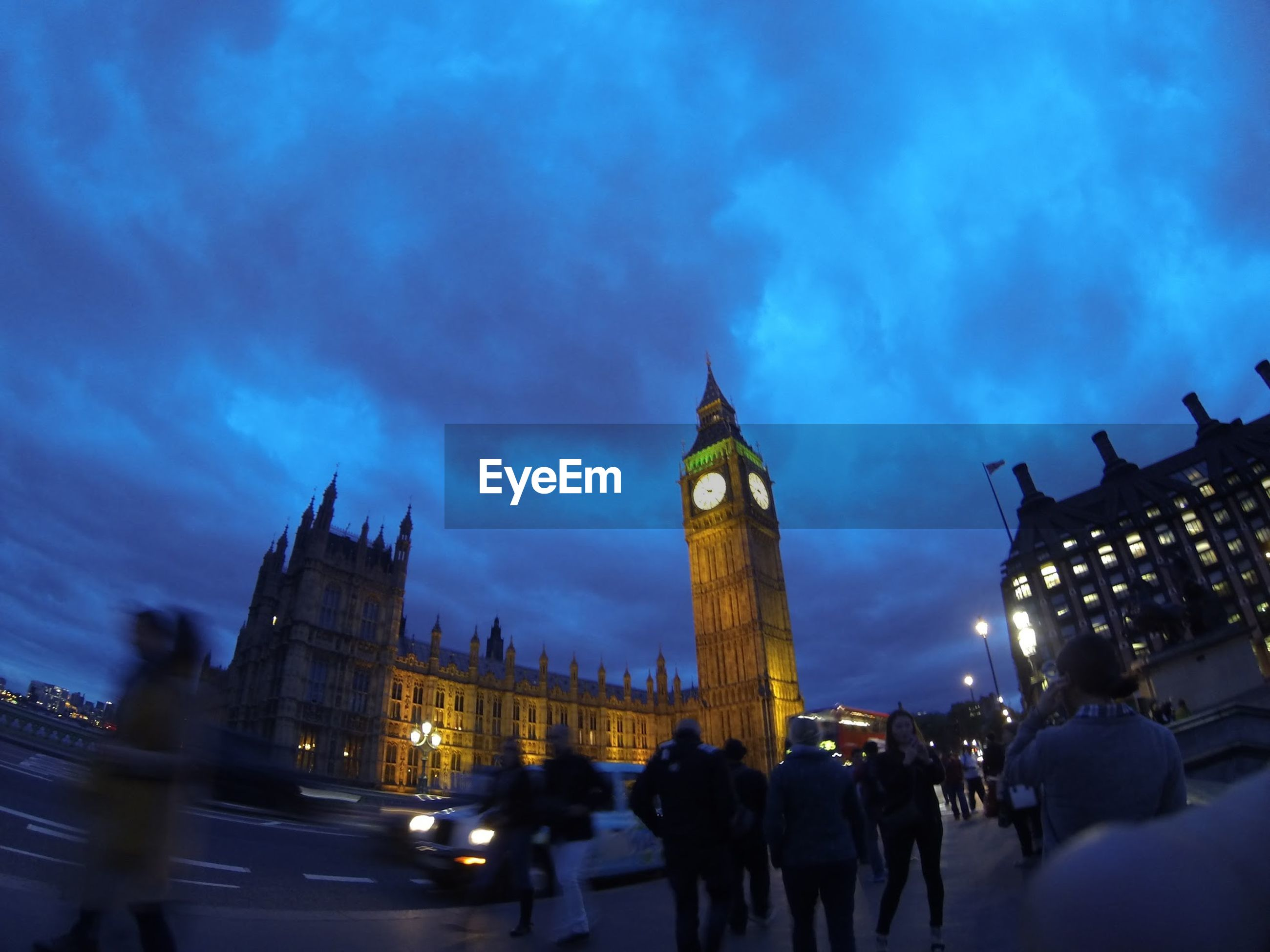 People at illuminated big ben tower against sky