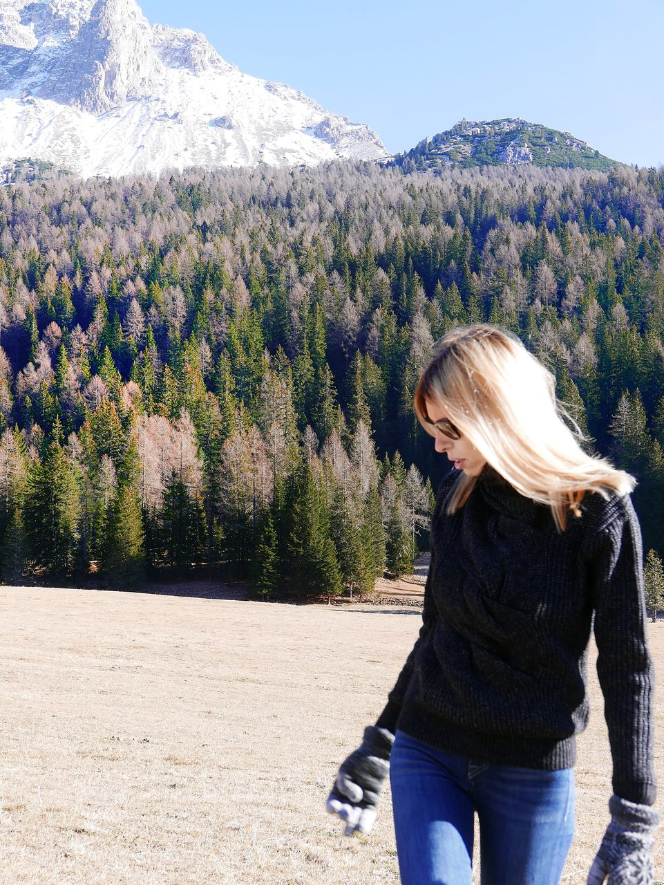 Young woman standing on mountain against sky