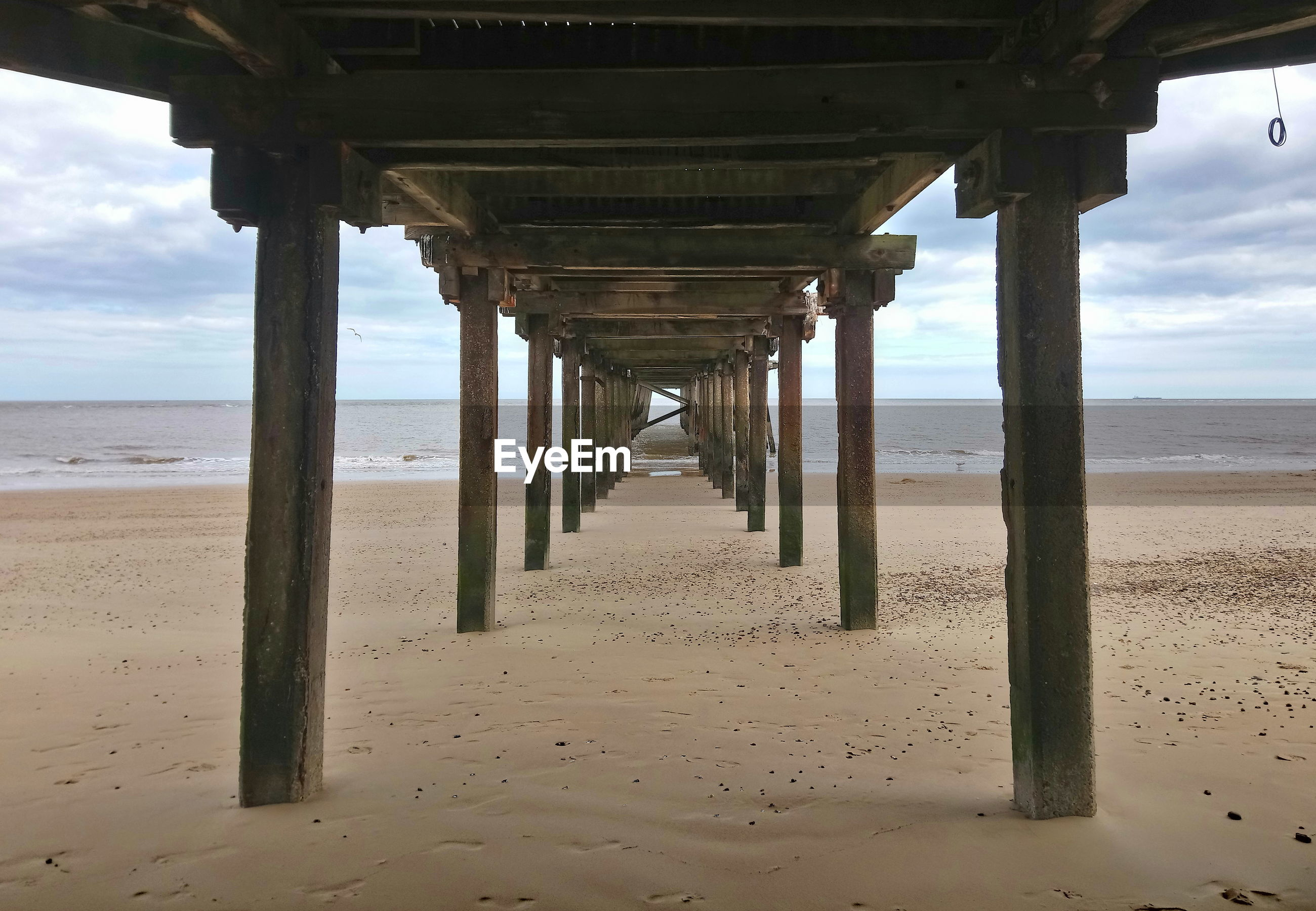 View of pier on beach against sky