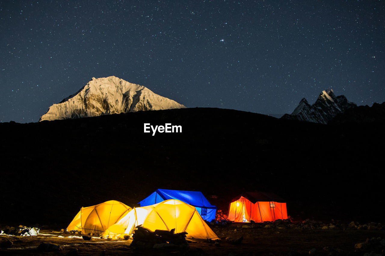SCENIC VIEW OF ILLUMINATED MOUNTAIN AGAINST SKY