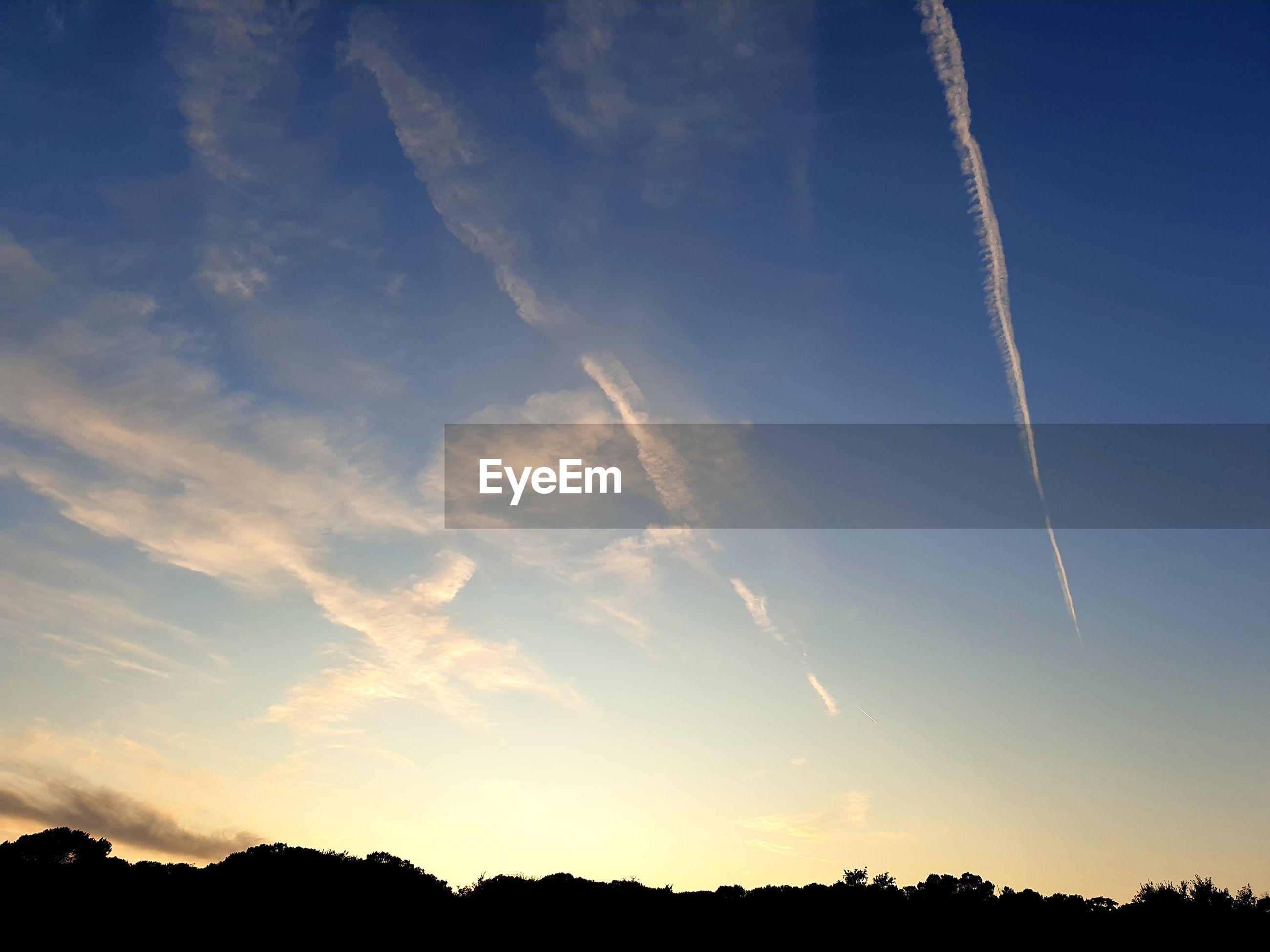 LOW ANGLE VIEW OF SILHOUETTE VAPOR TRAIL IN SKY