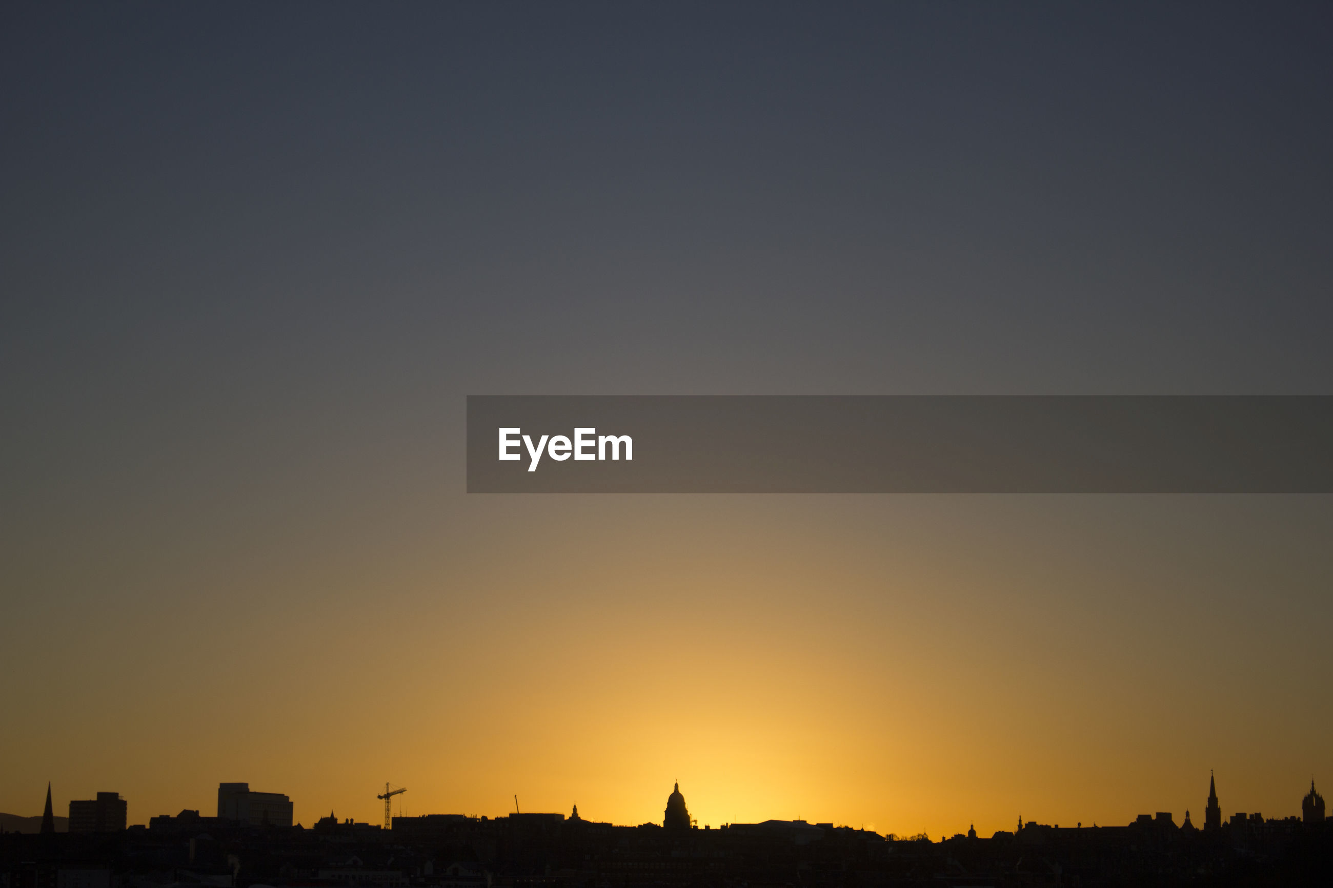 Silhouette of city against clear sky at sunset