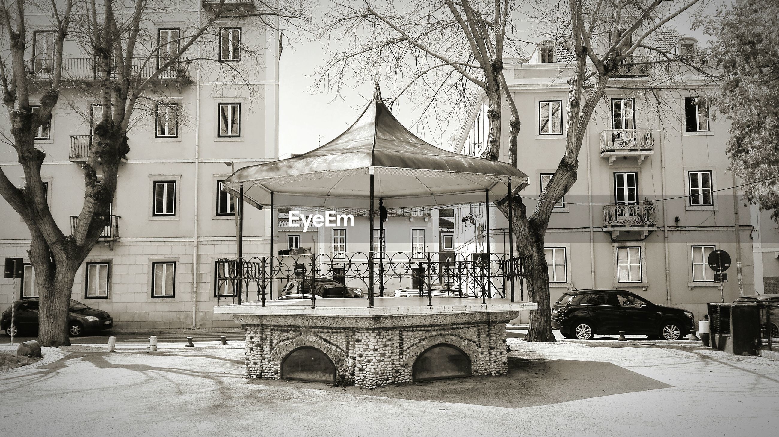 Gazebo against buildings and bare trees on sunny day