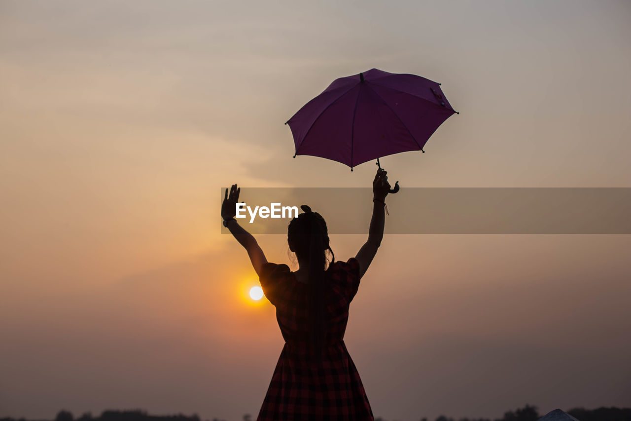 sunset, sky, real people, one person, lifestyles, women, silhouette, leisure activity, human arm, orange color, beauty in nature, holding, standing, adult, nature, arms raised, sun, cloud - sky, protection, outdoors, human limb