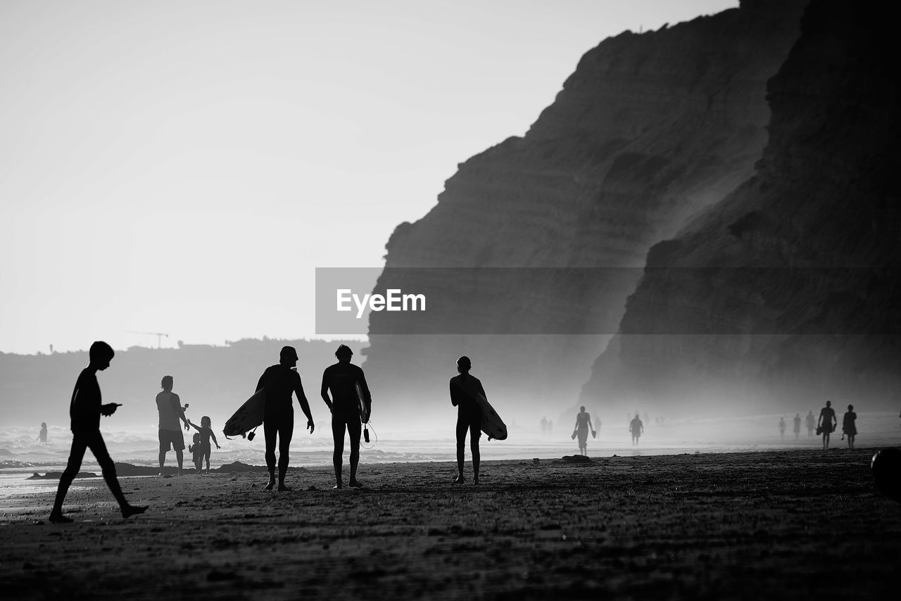 Silhouette people with surfboards at beach against sky