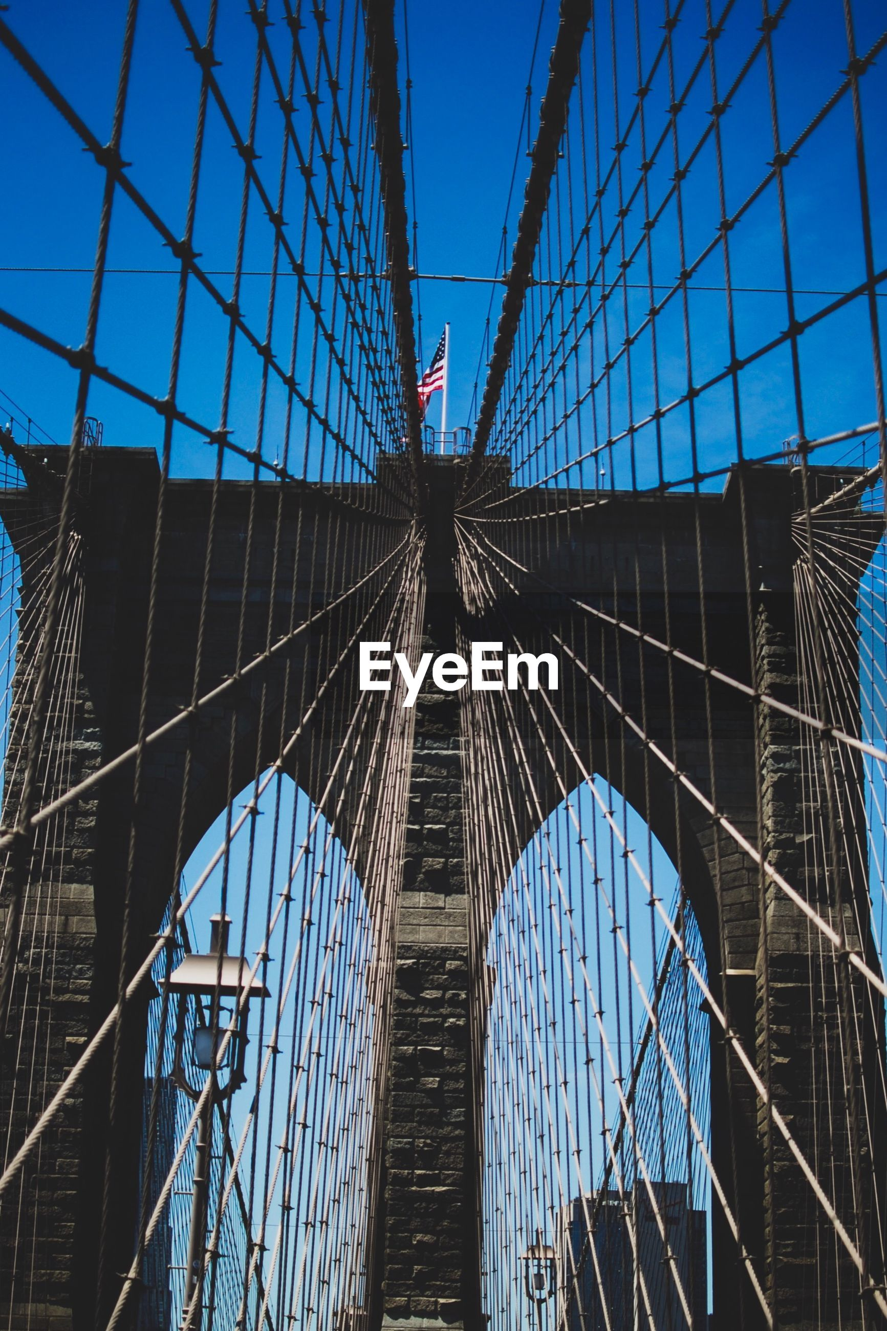 LOW ANGLE VIEW OF SUSPENSION BRIDGE IN CITY