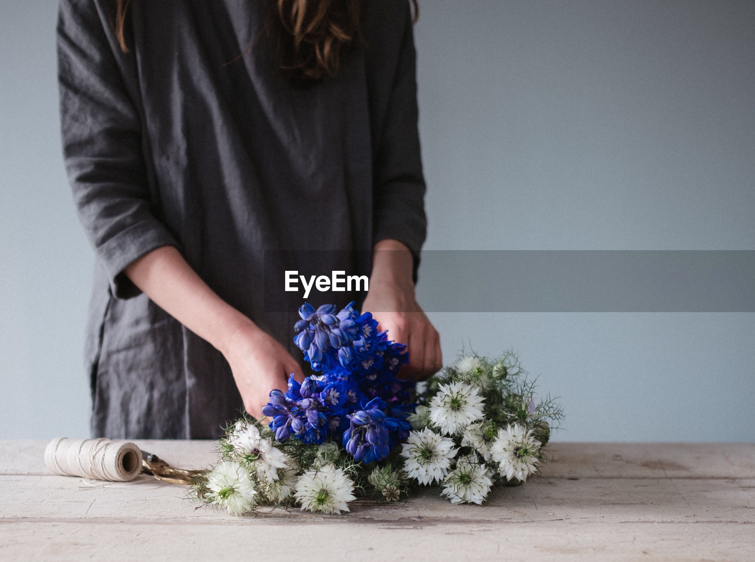 Midsection of woman tying flowers at table against wall
