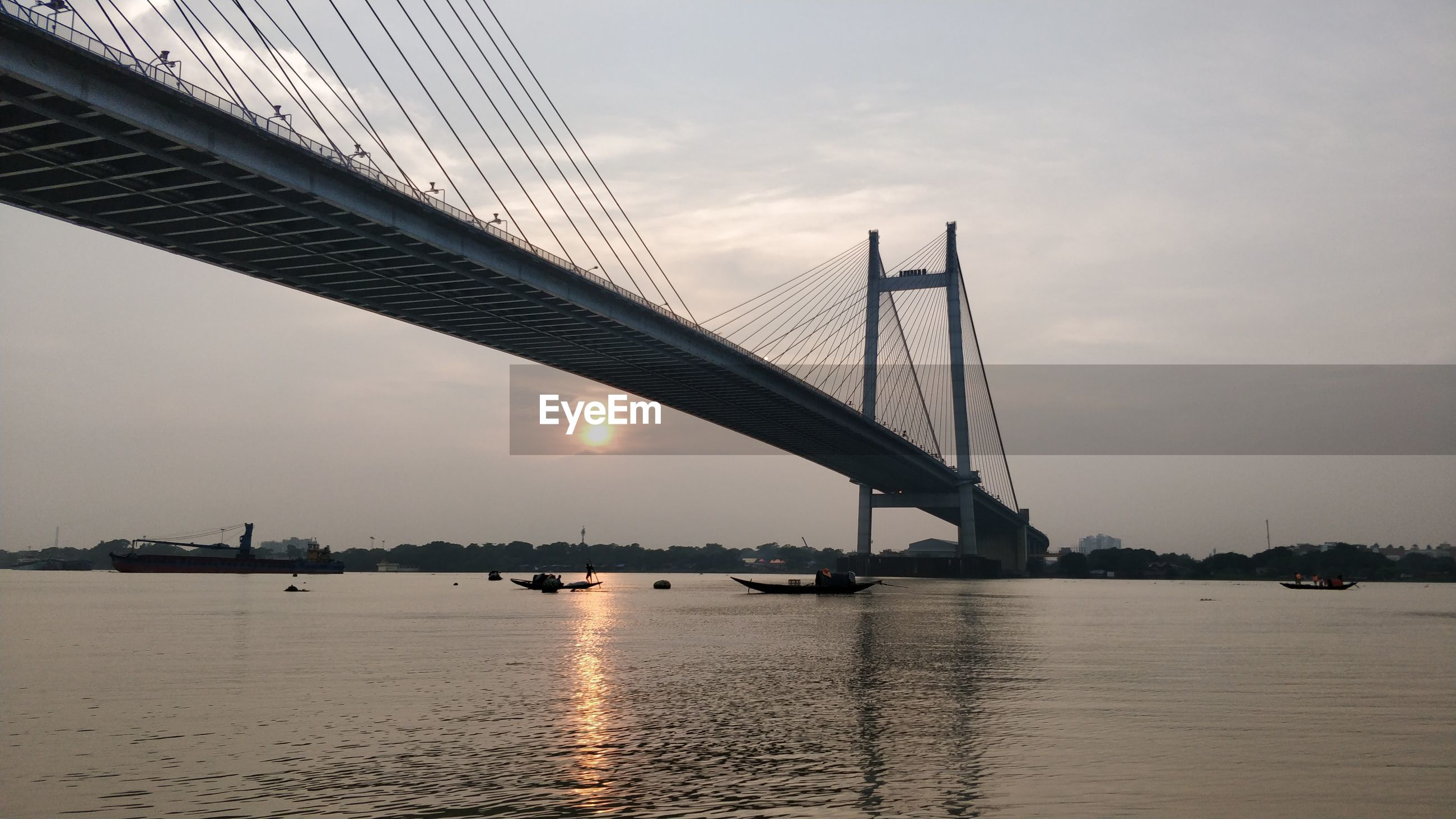 View of bridge over river at sunset