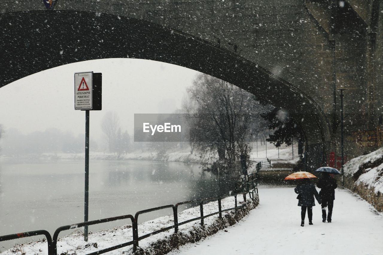 People Walking On Road By Frozen River In City