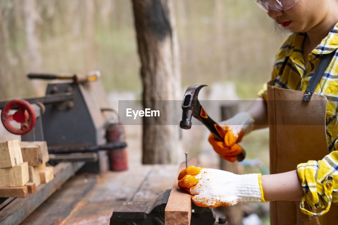 real people, human hand, focus on foreground, one person, human body part, hand, holding, lifestyles, wood - material, day, food, food and drink, men, leisure activity, occupation, close-up, burning, preparation, fire, finger